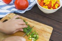 Κλείστε επάνω των χεριών γυναικών που μαγειρεύουν τη φυτική σαλάτα στην κουζίνα στον ξύλινο πίνακα Υγιές γεύμα, και χορτοφάγα τρό στοκ εικόνες