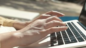 Κλείστε επάνω των χεριών γυναικών ` s δακτυλογραφώντας σε έναν φορητό προσωπικό υπολογιστή υπαίθρια απόθεμα βίντεο