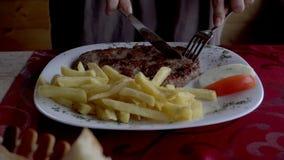 Κλείστε επάνω των χεριών γυναικών ` s κόβοντας το πιάτο κρέατος στο πιάτο στο εστιατόριο φιλμ μικρού μήκους