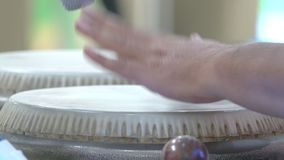 Κλείστε επάνω των χεριών ενός ατόμου που παίζει μια κρούση τυμπάνων απόθεμα βίντεο