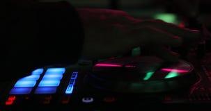 Κλείστε επάνω των χεριών ενός DJ που παίζει σε έναν ψηφιακό ελεγκτή σε ένα σκοτεινό νυχτερινό κέντρο διασκέδασης απόθεμα βίντεο