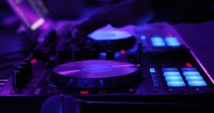 Κλείστε επάνω των χεριών ενός DJ που παίζει σε έναν ψηφιακό ελεγκτή φιλμ μικρού μήκους