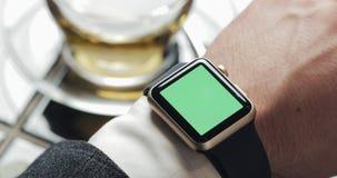 Κλείστε επάνω των χεριών επιχειρησιακών ατόμων με το πράσινο κλειδί χρώματος οθόνης smartwatch Άνετος καφές στο υπόβαθρο απόθεμα βίντεο