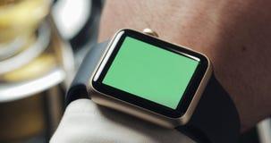 Κλείστε επάνω των χεριών επιχειρησιακών ατόμων με το πράσινο κλειδί χρώματος οθόνης smartwatch Άνετος καφές στο υπόβαθρο φιλμ μικρού μήκους