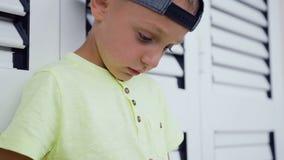 Κλείστε επάνω των χεριών και του προσώπου χρονών του αγοριού 5-6 που παίζοντας παιχνίδι online στο smartphone που στέκονται κοντά απόθεμα βίντεο