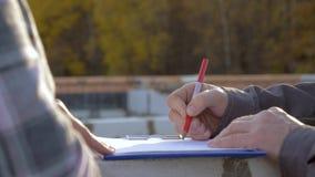 Κλείστε επάνω των χεριών των οικοδόμων επισύρει την προσοχή ένα μολύβι στο σχέδιο της κατασκευής απόθεμα βίντεο