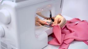 Κλείστε επάνω των χεριών της needlewoman εργασίας με τη ράβοντας μηχανή στην προσαρμογή του στούντιο Διαδικασία το ρόδινο ύφασμα απόθεμα βίντεο