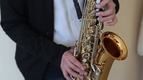 Κλείστε επάνω των χεριών του αρσενικού παίζοντας το saxophone απόθεμα βίντεο