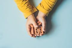 Κλείστε επάνω των χεριών του παιδιού παίζοντας με τα πραγματικά μικρά τούβλα αργίλου Στοκ φωτογραφία με δικαίωμα ελεύθερης χρήσης