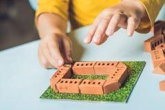 Κλείστε επάνω των χεριών του παιδιού παίζοντας με τα πραγματικά μικρά τούβλα αργίλου Στοκ εικόνα με δικαίωμα ελεύθερης χρήσης