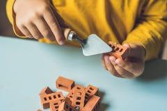 Κλείστε επάνω των χεριών του παιδιού παίζοντας με τα πραγματικά μικρά τούβλα αργίλου Στοκ Φωτογραφία