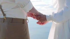 Κλείστε επάνω των χεριών newlyweds κρατώντας ήπια ο ένας τον άλλον φιλμ μικρού μήκους