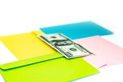 Κλείστε επάνω των χρημάτων στο ρόδινο φάκελο βρίσκεται στους πολυ χρωματισμένους φακέλους και τις επιστολές ως υπόβαθρο Χλεύη μαρ στοκ εικόνες