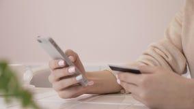 Κλείστε επάνω των όμορφων αγορών γυναικών on-line με την πιστωτική κάρτα και το smartphone στο σπίτι 60 fps απόθεμα βίντεο