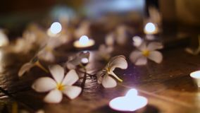 Κλείστε επάνω, όμορφο ντεκόρ νύχτας στο πάτωμα, τακτοποιημένα κεριά και σχεδιασμένα λουλούδια, άσπρα magnolias, ρομαντικά φιλμ μικρού μήκους