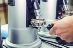 Κλείστε επάνω Barista παίρνει το άλεσμα καφέ στην ομάδα, προετοιμάζεται στην παρασκευή του πυροβολισμού espresso Εκλεκτική εστίασ στοκ εικόνες
