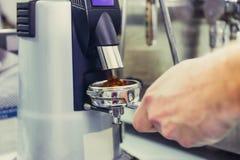 Κλείστε επάνω Barista παίρνει το άλεσμα καφέ στην ομάδα, προετοιμάζεται στην παρασκευή του πυροβολισμού espresso Εκλεκτική εστίασ στοκ εικόνες με δικαίωμα ελεύθερης χρήσης