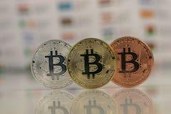 Κλείστε επάνω Bitcoins, χρυσός bitcoin, ασημένιοι bitcoin και χαλκός bitcoin με το θολωμένο υπόβαθρο των παγκόσμιων σημαιών Ανταν στοκ φωτογραφία