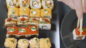 Κλείστε επάνω chopsticks κρατά το gunkan ρόλο maki σουσιών πέρα από ένα σύνολο πιάτων ή πιατελών Εξυπηρετημένος στο ιαπωνικό εστι απόθεμα βίντεο