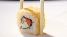 Κλείστε επάνω chopsticks που παίρνουν τη μερίδα του ρόλου σουσιών στο επιτραπέζιο εστιατόριο απόθεμα βίντεο