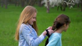 Κλείστε νέο όμορφο κοτσίδων επάνω πλεξίματος λίγη φίλη hairstyles υπαίθρια απόθεμα βίντεο