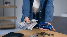 Κλείστε τα αυξημένα θηλυκά χέρια με τα χρήματα σε ένα δίνει και το αυτοκίνητο παιχνιδιών σε άλλο φιλμ μικρού μήκους