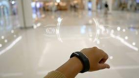 Κλείστε τα αυξημένα χέρια της γυναίκας χρησιμοποιώντας το έξυπνο ρολόι με το ενδιάμεσο με τον χρήστη HUD για τη φουτουριστικές εφ απόθεμα βίντεο