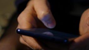 Κλείστε τα δάχτυλα των γυναικών καταναλώνει το smartphone στη νύχτα κορίτσι που κοιτάζει βιαστικά Διαδίκτυο σε ένα κινητό τηλέφων φιλμ μικρού μήκους