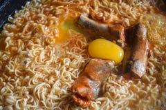 Κλείστε τα επάνω κονσερβοποιημένα επικασσιτερωμένα ψάρια και την το αυγό στο στιγμιαίο νουντλς κατά μαγείρεμα από το βραστό νερό στοκ εικόνα