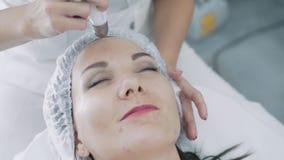 Κλείστε τα χέρια cosmetologist αποτελεί την επεξεργασία δερμάτων στο πρόσωπο γυναικών στο σαλόνι ομορφιάς, σε αργή κίνηση απόθεμα βίντεο