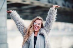 Κλείστε την αυξημένη μοντέρνη ευτυχή νέα γυναίκα στοκ εικόνες