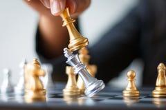 Κλείστε το αυξημένο χέρι της επιχειρησιακής γυναίκας που κινεί το χρυσό σκάκι προς το defe Στοκ Εικόνες
