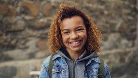 Κλείστε το σε αργή κίνηση πορτρέτο του γελώντας κοριτσιού αφροαμερικάνων με την ελαφριά σγουρή τρίχα στο σακάκι τζιν που εξετάζει απόθεμα βίντεο