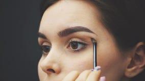 Κλείστε το όμορφο πρόσωπο του νέου κοριτσιού για να πάρετε το makeup Γυναίκα που εφαρμόζει τη σκιά ματιών στα φρύδια της με μια β φιλμ μικρού μήκους