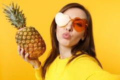 Κλείστε selfie αυξημένος της νέας γυναίκας στα γυαλιά καρδιών που φυσούν που στέλνουν το φιλί αέρα, φρέσκα φρούτα ανανά λαβής που στοκ φωτογραφία