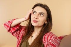 Κλείστε selfie αυξημένος της σκεπτικής νέας γυναίκας στα περιστασιακά ενδύματα που κοιτάζει κατά μέρος, που βάζει το χέρι στο κεφ στοκ φωτογραφίες