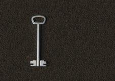 Κλειδί μετάλλων σε ένα υπόβαθρο ταπήτων Στοκ φωτογραφίες με δικαίωμα ελεύθερης χρήσης