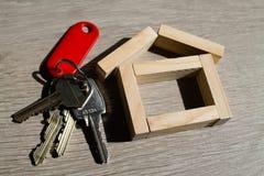 Κλειδί σπιτιών με ένα ξύλινο σπίτι στοκ εικόνες