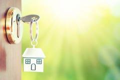 Κλειδί σπιτιών στην πόρτα με το πράσινο υπόβαθρο στοκ φωτογραφίες