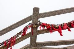 Κλειδαριά και κόκκινες κορδέλλες σε μια ράγα φρουράς στο κίτρινο βουνό Κίνα Στοκ Εικόνα
