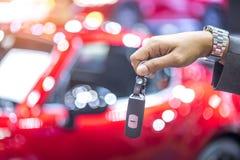 Κλειδιά αυτοκινήτων εκμετάλλευσης χεριών με το θολωμένο υπόβαθρο αυτοκινήτων Στοκ εικόνες με δικαίωμα ελεύθερης χρήσης