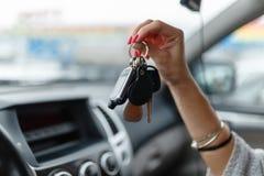 Κλειδιά αυτοκινήτων στο χέρι ενός κοριτσιού στο εσωτερικό αυτοκινήτων Γυναίκα holdin στοκ εικόνες