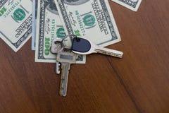 Κλειδιά και αμερικανικοί λογαριασμοί εκατό δολαρίων στο ξύλινο γραφείο Στοκ φωτογραφία με δικαίωμα ελεύθερης χρήσης