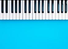 Κλειδιά πληκτρολογίων πιάνων συνθετών μουσικής στο μπλε Στοκ Φωτογραφία