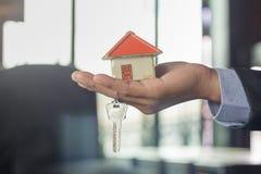 Κλειδιά σπιτιών παράδοσης κτηματομεσιτών, έννοια ακίνητων περιουσιών, Ho στοκ εικόνα με δικαίωμα ελεύθερης χρήσης
