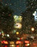 Κλειστές επάνω σταγόνες βροχής στον ανεμοφράκτη αυτοκινήτων κατά τη διάρκεια μιας οδήγησης στην αστική οδό τη νύχτα Στοκ εικόνες με δικαίωμα ελεύθερης χρήσης