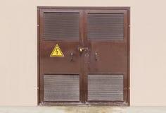Κλειστή ηλεκτρικός υποσταθμός πόρτα με το σημάδι υψηλής τάσης στοκ εικόνες