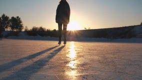 ΚΛΕΙΣΤΕ ΕΠΑΝΩ, ΧΑΜΗΛΗ ΑΠΟΨΗ ΓΩΝΙΑΣ: Ευτυχές γυναικών γρήγορα στην παγωμένη λίμνη στο τοπικό πάρκο στο χρυσό ηλιοβασίλεμα στα μαγι απόθεμα βίντεο