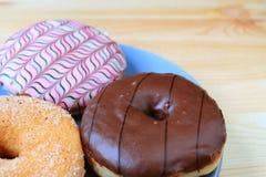 Κλειστός επάνω τρεις τύπους νόστιμα doughnuts εξυπηρέτησε στον ξύλινο πίνακα με την εκλεκτική εστίαση στοκ φωτογραφίες με δικαίωμα ελεύθερης χρήσης