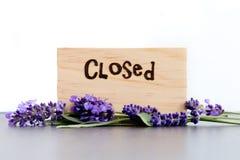 Κλειστός - η λέξη που καίγεται στο ξύλο με πορφυρό lavender ανθίζει στην πλάκα με το άσπρο υπόβαθρο στοκ εικόνες